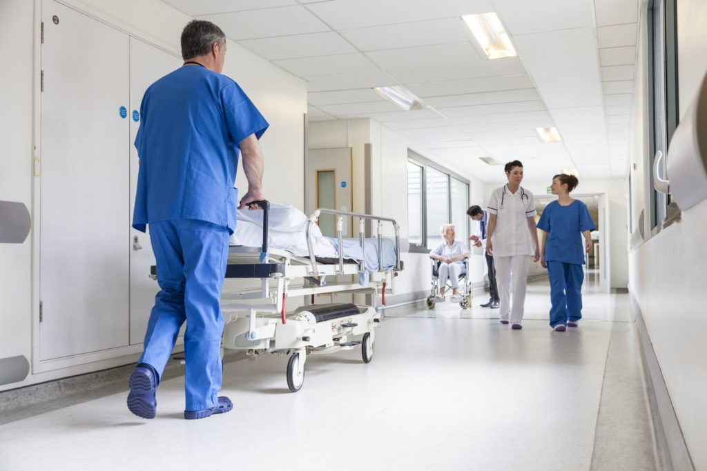 20705732 - male nurse pushing stretcher gurney bed in hospital corridor with doctors & senior female patient